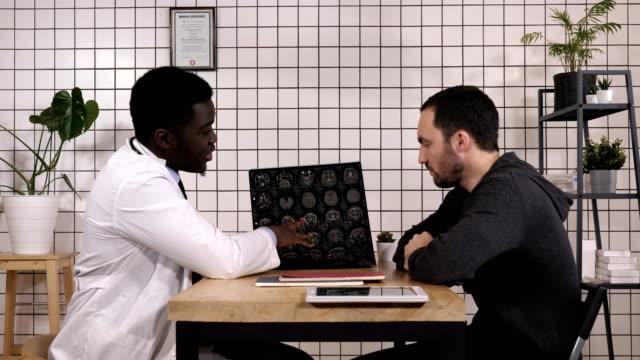 Profesional-de-la-salud-intelectual-con-blanco-labcoat-mostrando-resonancia-magnética-al-paciente
