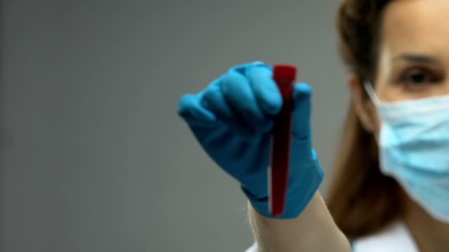 Doctora-sujetando-el-tubo-de-ensayo-con-conciencia-de-enfermedad-infecciosas-muestra-de-sangre