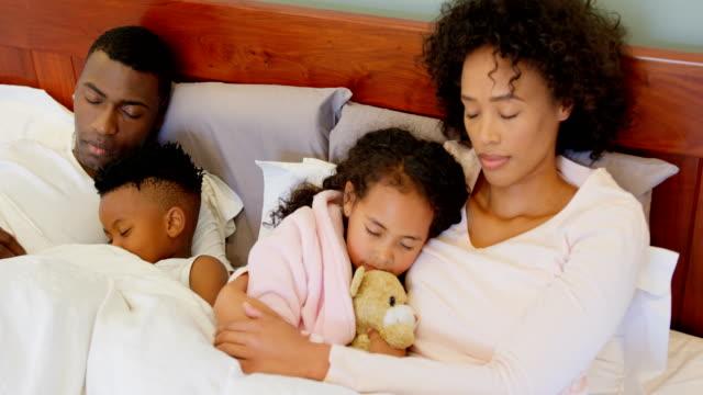 Vista-frontal-de-la-familia-black-para-dormir-en-el-dormitorio-en-casa-4k