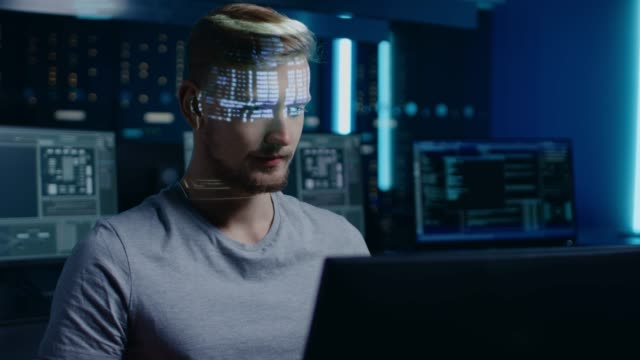 Handsome-Young-Software-Developer-Working-on-Personal-Computer-in-Digital-Identity-Cyber-Security-Data-Center-Program-Coding-Language-Reflects-on-His-Face-Futuristic-Hacking-and-Programming-Concept