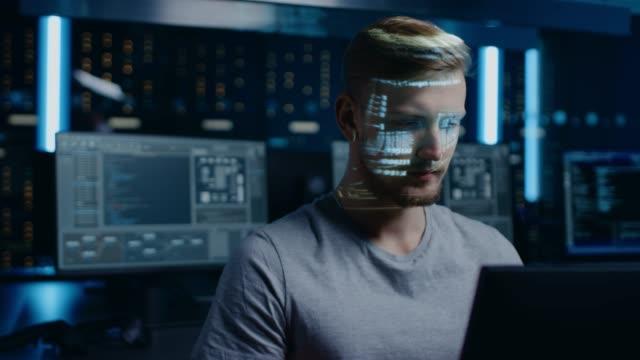 Retrato-de-joven-desarrollador-de-software-trabajando-en-el-ordenador-en-la-identidad-digital-centro-de-datos-de-seguridad-cibernética-programa-proyectado-lenguaje-de-codificación-se-refleja-en-su-rostro-Concepto-de-hacking-y-programación-futurista