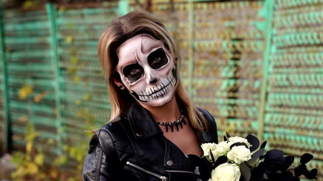 Novia-espeluznante-con-un-ramo-de-flores-negras-y-maquillaje-en-forma-de-un-cráneo
