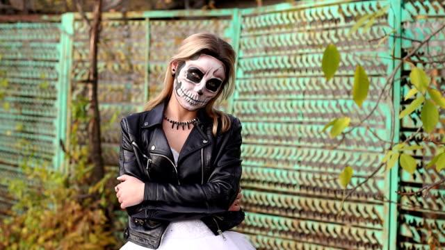 Chica-en-una-chaqueta-de-cuero-con-maquillaje-para-Halloween-en-el-fondo-de-una-vieja-cerca