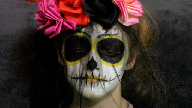 Little-girl-with-Day-of-the-Dead-make-up-and-Costume-Halloween-makeup-ideas-concept