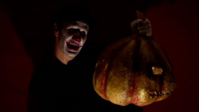 El-payaso-aterrador-tiene-una-máscara-de-calabaza-en-sus-manos-Un-hombre-aterrador-con-maquillaje-de-payaso-sostiene-una-calabaza-para-Halloween-Un-payaso-de-miedo-tiene-un-Jack-O-Lantern-en-sus-manos-con-ojos-luminosos-y-una-boca-