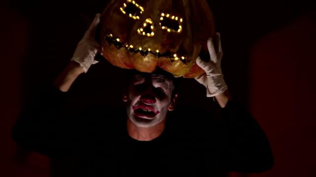 El-hombre-aterrador-en-la-composición-de-un-payaso-sostiene-una-calabaza-para-Halloween-y-se-la-pone-en-la-cabeza-Un-payaso-terrible-se-pone-una-máscara-en-forma-de-calabaza-en-la-cabeza-Terrible-payaso-sostiene-en-sus-manos-un-Jack-O-Lantern-con-ojos-