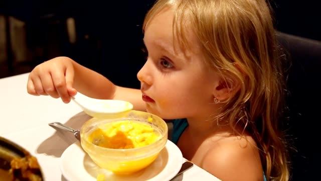Child-little-girl-eating-dessert-by-spoon-