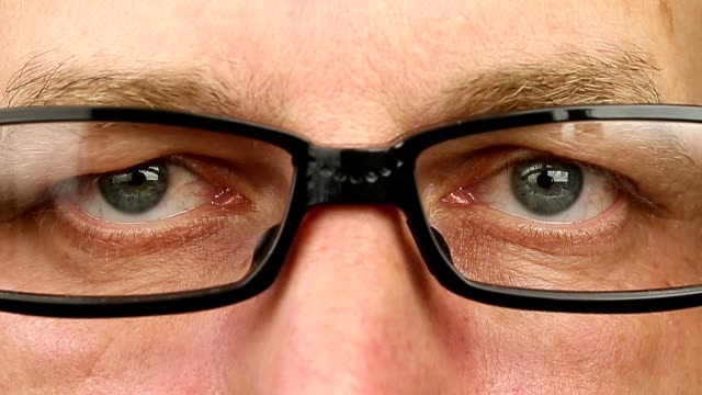 Caucasian-man-in-eyeglasses-extremely-close-up-view-Thinking-looking-around-Eye-movement-side-to-side-Corner-of-eyes-Smiling-laughing-man-face-glasses-Think-read-see-down-up-and-side-eyes-motion