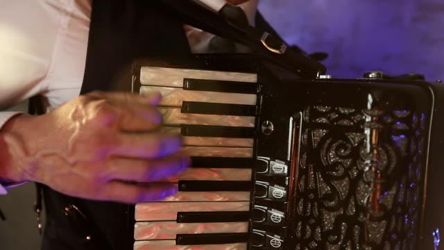 Un-músico-de-moda-en-una-camisa-blanca-toca-el-acordeón-en-el-estudio-