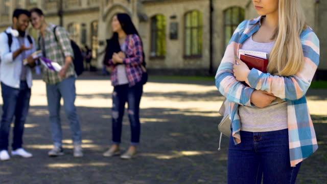 Estudiantes-riendo-y-señalando-a-la-niña-triste-solitaria-de-pie-a-un-lado-cruel-bulling