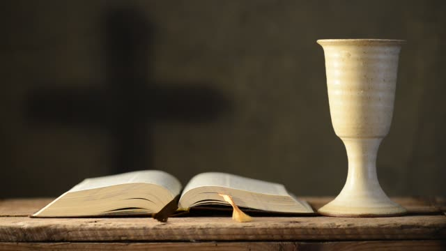open-bible-with-chalice-and-cross-shallow-depth-of-field-rack-focus