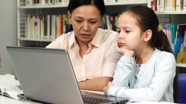 Mature-Asian-woman-helping-her-tired-daughter-with-homework