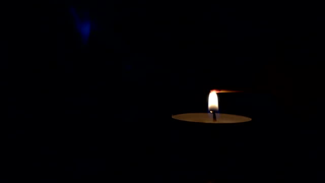 Lighting-a-match-stick-from-a-candle-in-the-dark-slow-motion