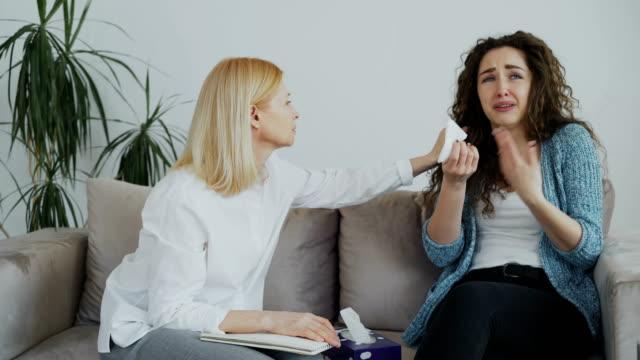 Psicólogo-experimentado-mujer-hablando-y-calmarse-deprimido-paciente-mujer-llora-durante-la-sesión-de-psicoterapia