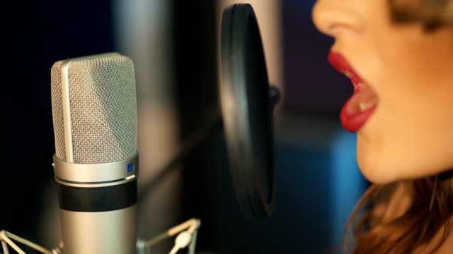 Young-woman-recording-a-song-in-a-professional-studio-