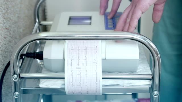 Médico-manos-colocación-electrodos-para-ECG