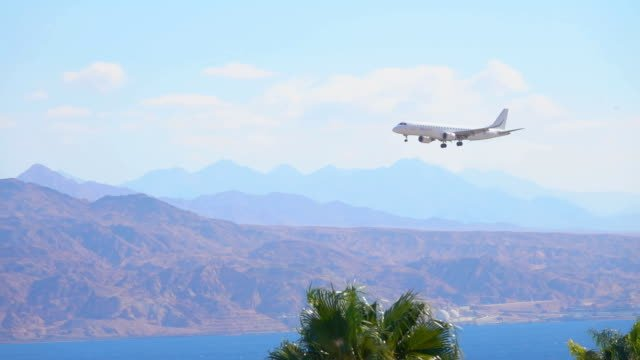 Plane-flies-over-the-sea-bay-and-prepars-to-land