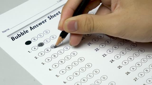 Mano-de-estudiante-asiática-haciendo-prueba-de-examen-con-la-forma-estandardizada-de-la-prueba-y-respuestas-burbujeadas-