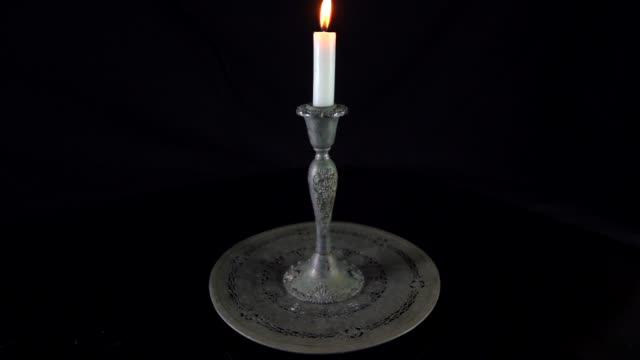 time-lapse-of-white-burning-candle-in-an-antique-victorian-silver-candle-holder