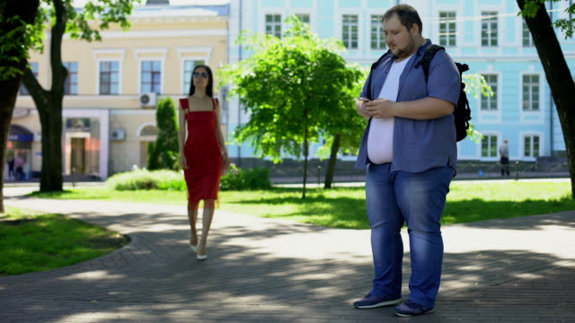 Obese-male-sadly-looking-at-pretty-slim-lady-in-dress-appearance-insecurities