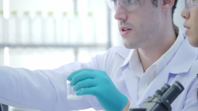 Dos-científicos-de-la-investigación-médica-en-mezclas-de-gafas-fumar-líquidos-en-un-vasos