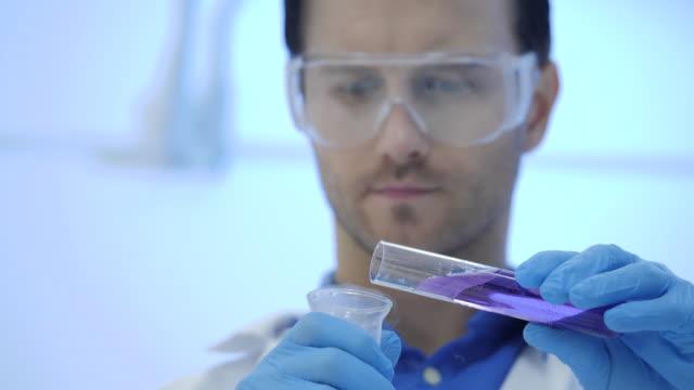Científicos-de-investigación-médica-masculina-en-mezclas-de-gafas-fumar-líquidos-en-un-vasos