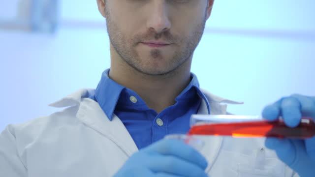 Científicos-de-investigación-médica-masculina-mezcla-líquidos-de-fumar-en-un-vasos