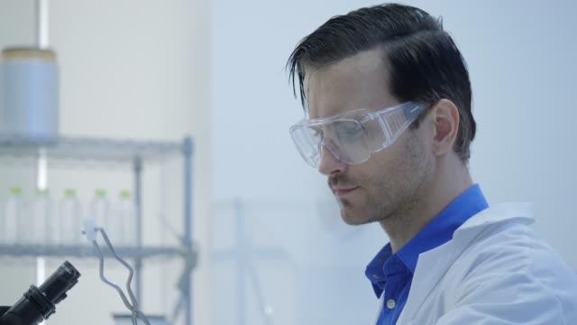 Investigadores-médicos-masculinos-ponen-hielo-seco-en-un-vaso-de-vidrio