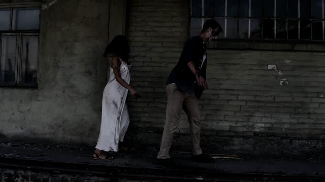 Concepto-de-horror-de-Halloween-Foto-de-fantasma-espeluznante-de-macho-y-hembra-o-zombie-caminando-con-heridos-cara-Una-vieja-casa-abandonada-en-el-fondo-Vista-lateral