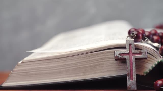 Bibel-und-Kreuz-Perlen-auf-einem-roten-Holztisch-Schönen-Hintergrund-Religion-Konzept-hautnah