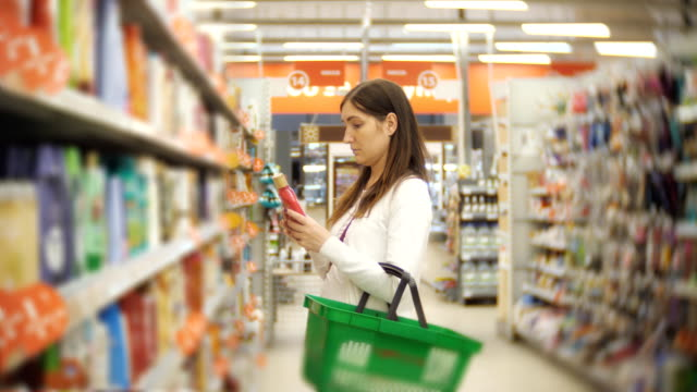 Young-caucasian-woman-buying-ethical-body-care-cream-products-in-supermarket-4K-