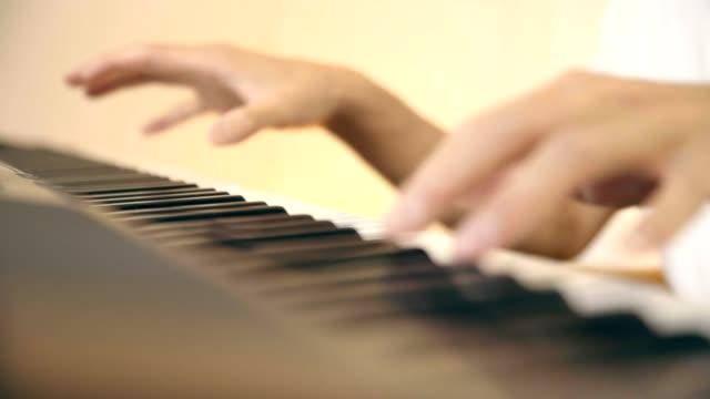 young-asian-musician-playing-keyboard