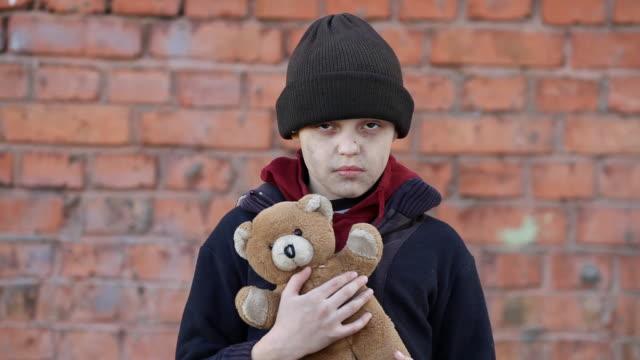 muchacho-sin-hogar-con-un-oso-de-peluche