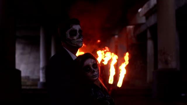 Pareja-en-ropa-de-la-boda-y-con-el-maquillaje-para-Halloween-están-parados-cerca-de-fuego-ardiente