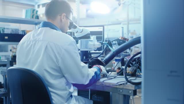 Trabajador-de-la-fábrica-de-electrónica-en-la-capa-de-blanco-trabajo-inspecciona-una-placa-de-circuito-impreso-a-través-de-un-microscopio-Digital-Instalación-de-fábrica-de-alta-tecnología-