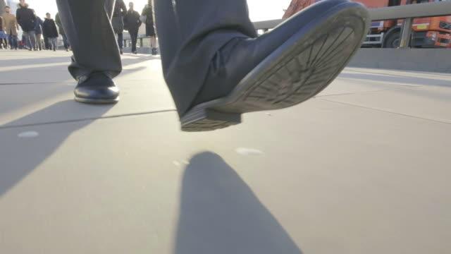 Vista-de-ángulo-bajo-de-pies-de-un-hombre-de-negocios-caminando