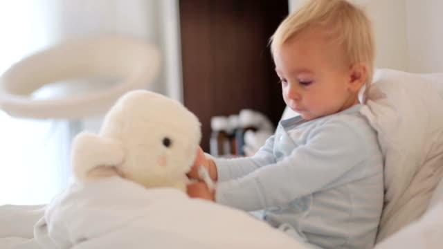 Madre-y-bebé-en-pijamas-temprano-en-la-mañana-mamá-cuidando-a-su-hijo-de-niño-enfermo-Bebé-en-la-cama-con-fiebre-y-nariz-corriente