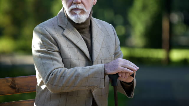 Elegant-senior-gentleman-massaging-his-wrestles-joint-problems-arthritis