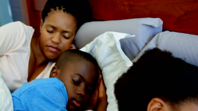Front-view-of-young-black-family-sleeping-together-on-bed-in-bedroom-of-comfortable-home-4k
