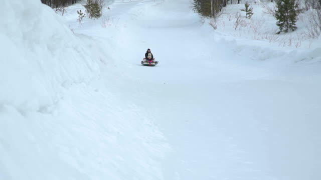 Woman-and-Girl-Riding-Fast-on-a-Snow-Tubing