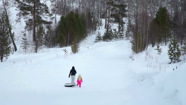 Woman-and-the-Girl-Climbing-a-Hill-with-Snow-Tube