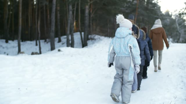 Large-Family-Walking-in-Snow-Covered-Forest