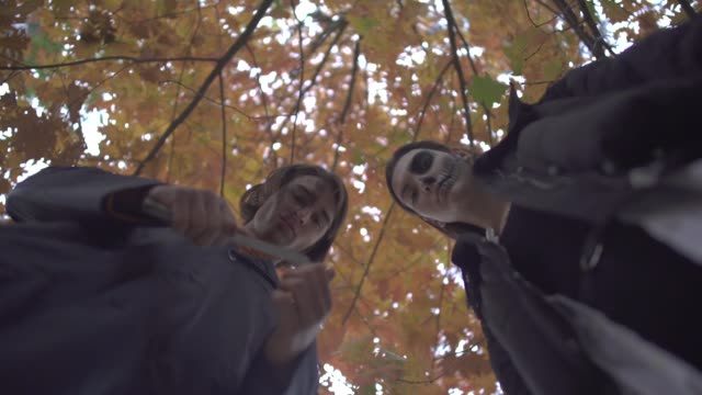 Two-people-with-a-hatchet-in-Halloween-costumes-looking-down-on-the-victim-with-serious-scary-faces-in-the-autumn-park