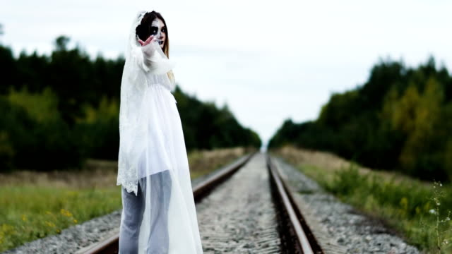 The-young-woman-with-make-up-of-dead-bride-for-Halloween-on-the-railway-track-4K