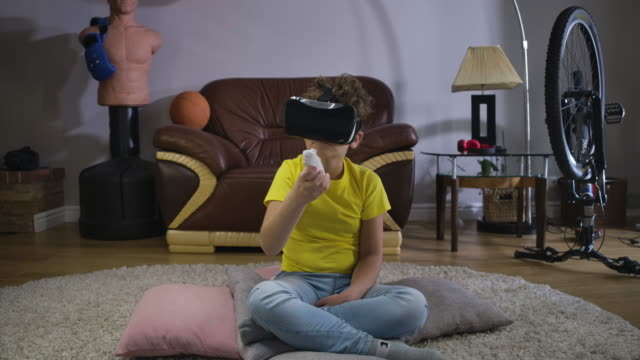 Little-boy-in-VR-googles-moving-hand-with-remote-control-and-looking-at-the-direction-of-controller-Caucasian-kid-in-casual-clothes-using-augmented-reality-indoors-Cinema-4k-ProRes-HQ-