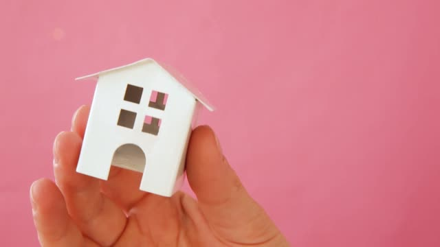 Simply-design-female-woman-hand-holding-miniature-white-toy-house-isolated-on-pink-pastel-colorful-trendy-background