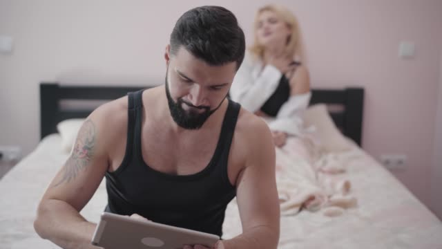 Blond-attractive-Caucasian-woman-sexually-moving-at-the-background-as-her-husband-or-boyfriend-playing-video-games-at-the-foreground-Young-games-addicted-guy-ignoring-intimate-life-
