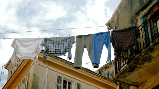 Clean-clothes-and-linen-hanging-on-a-clothesline-to-dry-outdoors-in-streets-4K