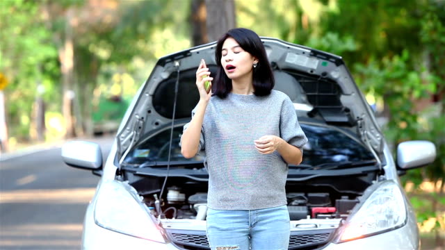 Woman-having-car-trouble-and-calling-technician