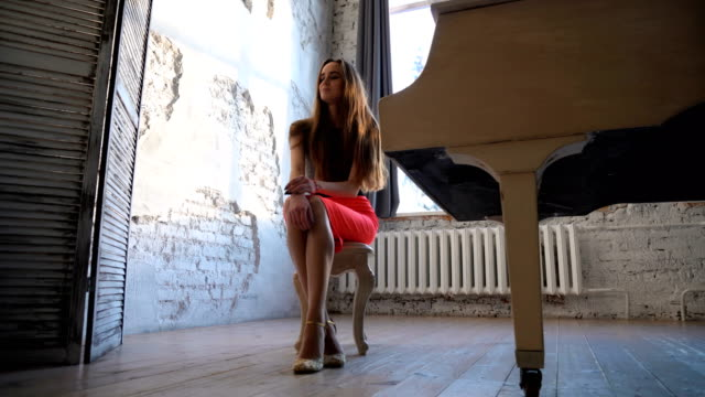 Attractive-young-woman-in-evening-dress-sitting-at-the-white-grand-piano